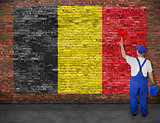 House painter paints flag of Belgium on brick wall