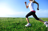 woman runner running on plain grass