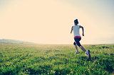 woman runner running on plain grass