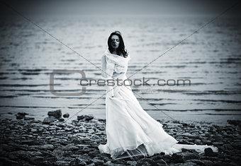 Beautiful sad girl in white dress standing on sea coast