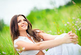 Happy smiling beautiful young woman sitting among grass and flowers