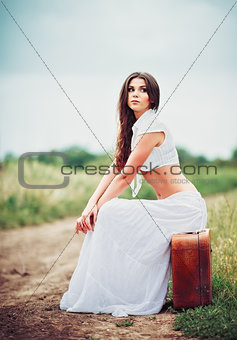 Beautiful young woman sits on suitcase near field road