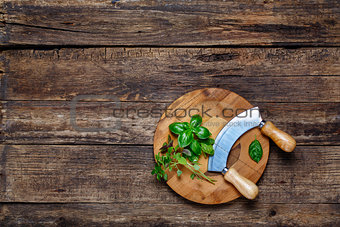 Fresh basil with mezzaluna cutting board