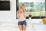informal girl , drinking coffee in kitchen