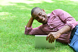 Smiling man lying on the lawn with tablet
