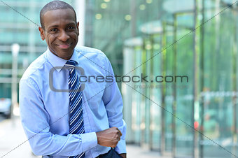 Corporate man poses casually at outdoor