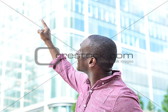 Casual man pointing with his finger to the building