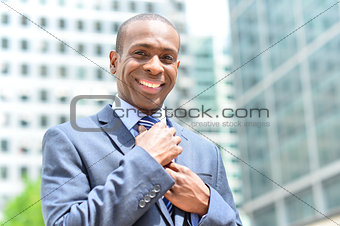 Businessman adjusting his collar outdoors