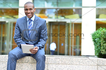 Smiling business executive using tablet