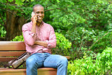 African man sitting on a bench, talking on phone