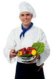 Chef holding fresh vegetables in strainer bowl