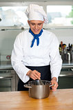Young male chef with whisk and mixing bowl