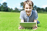 Young boy with tablet device at grassland