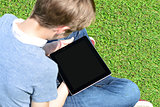Boy with touch pad sitting on meadow