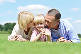 Smiling couple with daughter posing at outdoors