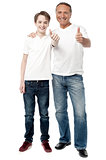 Smiling father and son showing thumps up