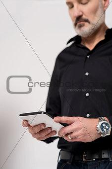 Mature man looking at his digital tablet