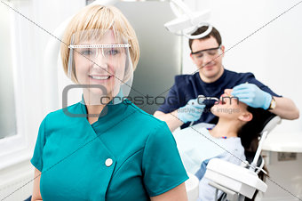 Male dentist with patient, in clinic.