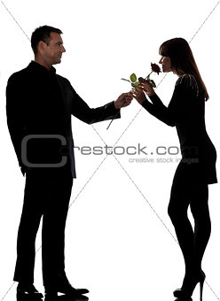 one couple man offering rose flower and woman smelling silhouett