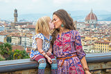 Mother and baby girl kissing against panoramic view of florence,