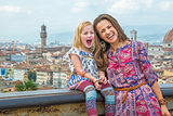 Portrait of smiling mother and baby girl against panoramic view