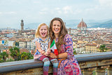 Happy mother and baby girl with flag against panoramic view of f