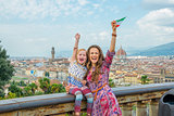 Happy mother and baby girl with flag rejoicing against panoramic