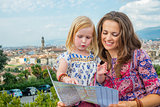 Happy mother and baby girl with map against panoramic view of fl