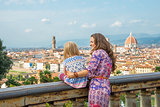 Mother and baby girl against panoramic view of florence, italy.