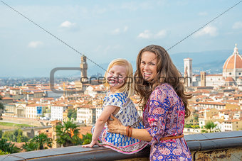 Portrait of happy mother and baby girl against panoramic view of