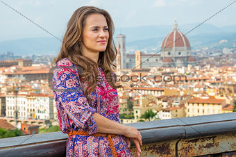 Portrait of thoughtful young woman against panoramic view of flo