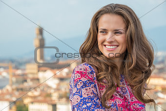 Portrait of smiling young woman against panoramic view of floren
