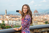 Happy young woman taking photo of panoramic view of florence, it