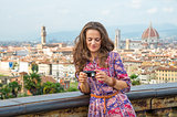 Young woman checking photos in camera against panoramic view of