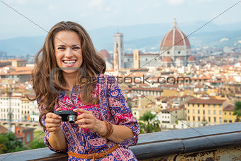 Portrait of happy young woman with photo camera against panorami