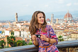 Young woman with photo camera against panoramic view of florence