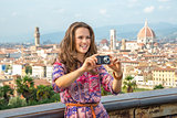 Smiling young woman taking photo against panoramic view of flore