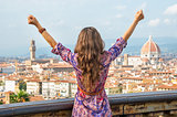 Young woman rejoicing against panoramic view of florence, italy