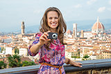 Happy young woman taking photo against panoramic view of florenc