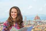 Portrait of happy young woman with map against panoramic view of