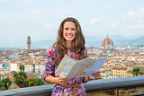 Happy young woman with map against panoramic view of florence, i