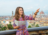Happy young woman with map pointing against panoramic view of fl