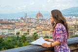 Young woman with map against panoramic view of florence, italy