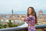 Young woman with map pointing on panoramic view of florence, ita