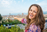 Smiling young woman pointing on panoramic view of florence, ital