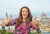 Smiling young woman showing thumbs up against panoramic view of