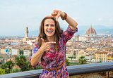 Happy young woman framing against panoramic view of florence, it