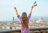 Young woman with flag rejoicing against panoramic view of floren