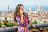 Happy young woman talking mobile phone against panoramic view of