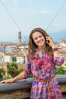 Portrait of smiling young woman talking mobile phone against pan